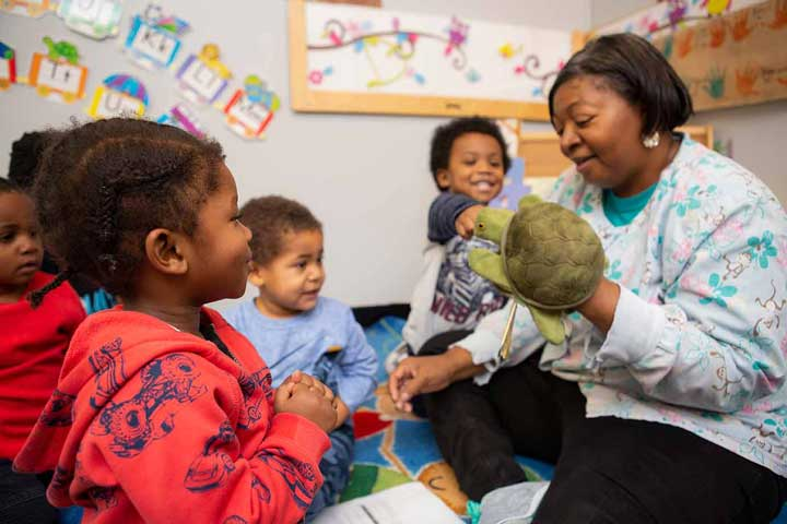 Teacher and children looking at a turtle puppet together.