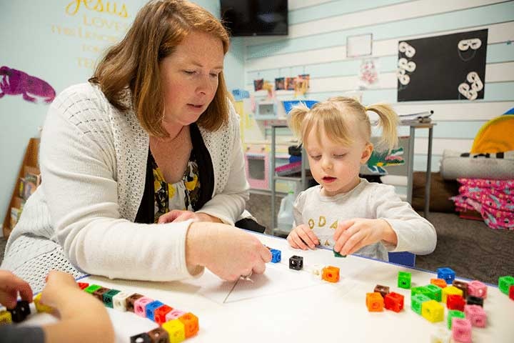 Preschool teacher helping a young child build a triangle with blocks.