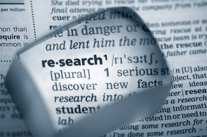 magnifiying glass highlight the word research in the dictionary.