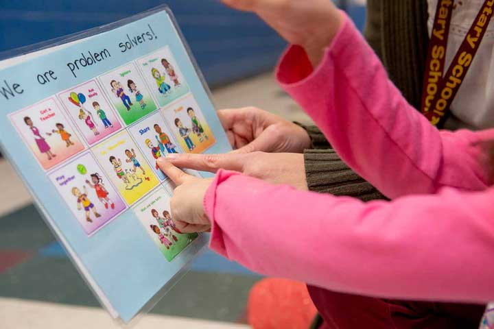 A child pointing at a choice cards on a sheet to solve a problem in the classroom.