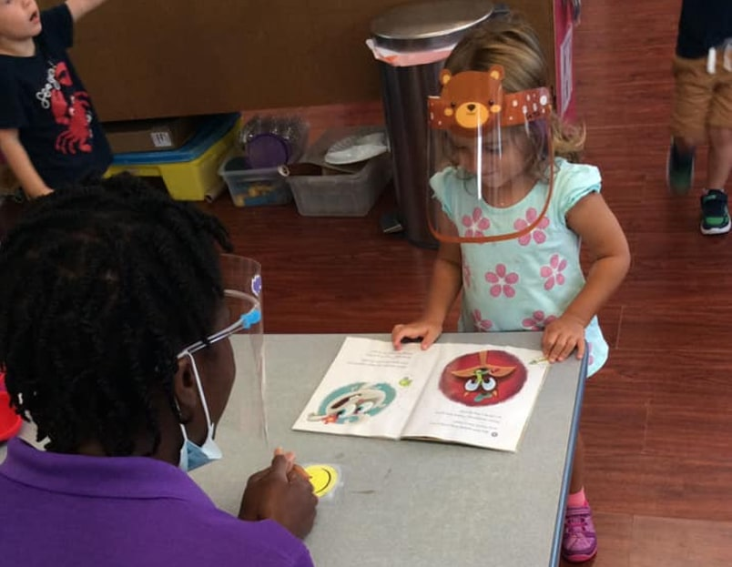 little girl wearing a face shield is reading a book and a teacher wearing a face shield is watching