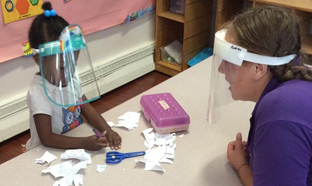 little girl wearing a face shield is coloring cut up paper and her teacher (also wearing a face shield) is talking to her